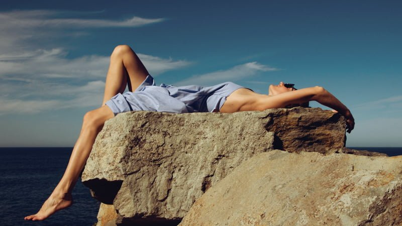 image of a women lying down on a big rock next to the ocean