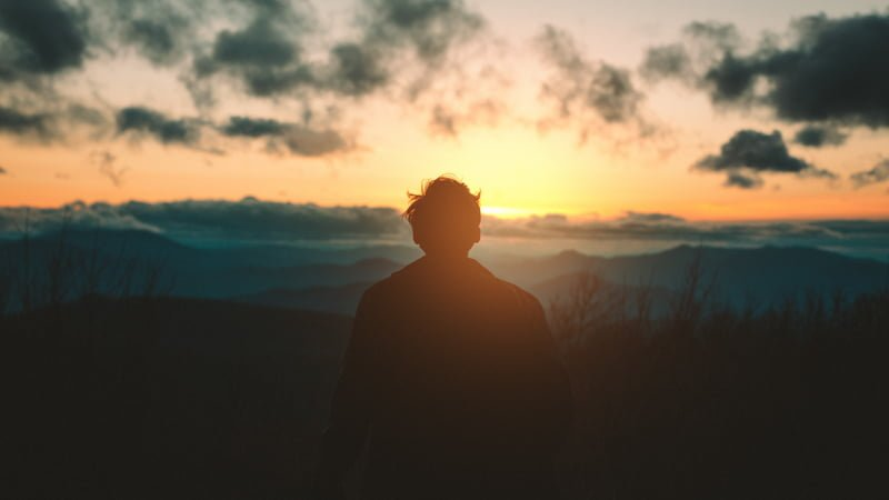 a person is meditating during sun rise