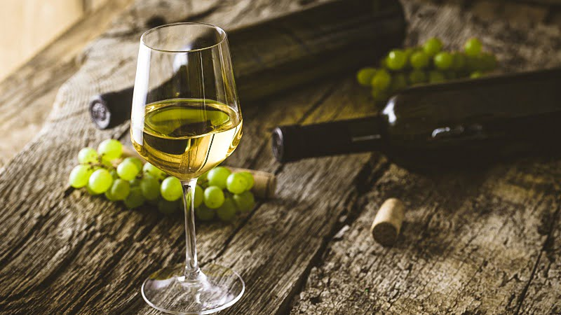 a glass of white wine in wine cellar with green grapes
