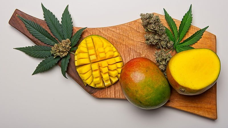 mangoes and cannabis leaves and buds on a wooden tray