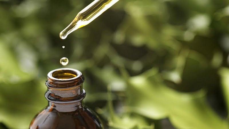 Terpenes oil drop from a dropper into a bottle
